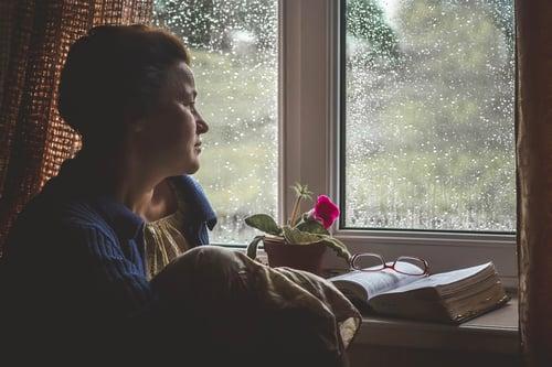 senior-woman-looking-outside-during-rain