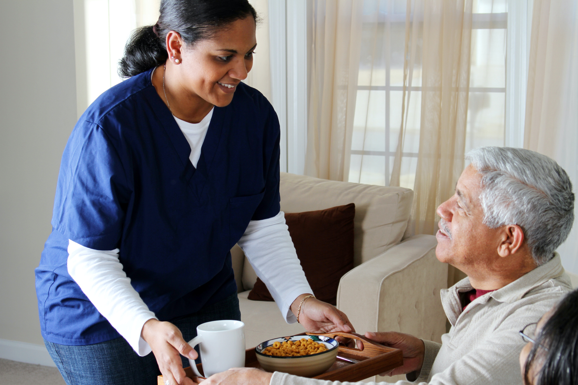 caregiver nurse serving senior food